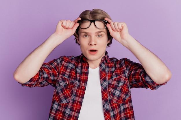 Ritratto di un ragazzo eccitato e scioccato che guarda la telecamera a bocca aperta toglie le specifiche su sfondo viola