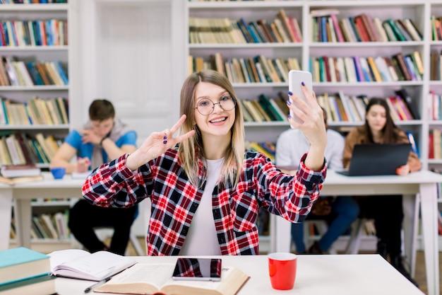 Ritratto di giovane donna bionda abbastanza sorridente eccitata in camicia a scacchi e occhiali facendo selfie foto e mostrando v-sign con due dita, seduto al tavolo nella sala di lettura della biblioteca