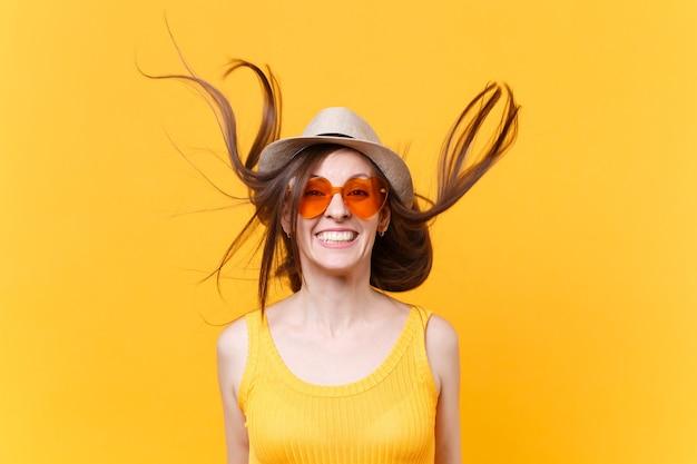Ritratto di giovane donna sorridente eccitata in cappello estivo di paglia, occhiali arancioni con capelli svolazzanti copia spazio isolato su sfondo giallo. persone sincere emozioni, concetto di stile di vita. zona pubblicità.