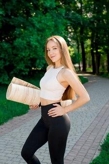 Ritratto dell'insegnante di yoga eccitato in posa con tappetino fitness, istruttore di fitness felice o allenatore in allenamento sport all'aria aperta