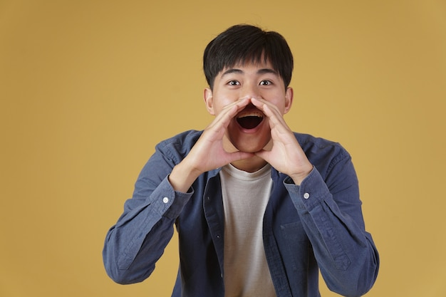 Il ritratto di giovane uomo asiatico eccitato si è vestito con indifferenza con l'annuncio che grida tenendosi per mano vicino alla bocca isolata