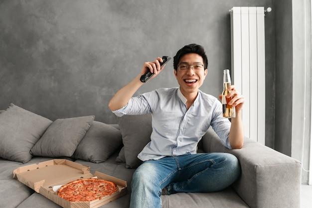 Ritratto di un giovane uomo asiatico eccitato tenendo la bottiglia da birra