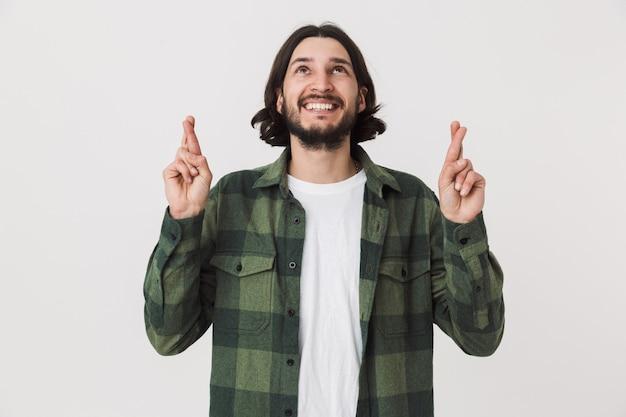 Ritratto di un giovane uomo brunetta barbuto eccitato che indossa una camicia a quadri in piedi isolato su un muro bianco, tenendo le dita incrociate per buona fortuna