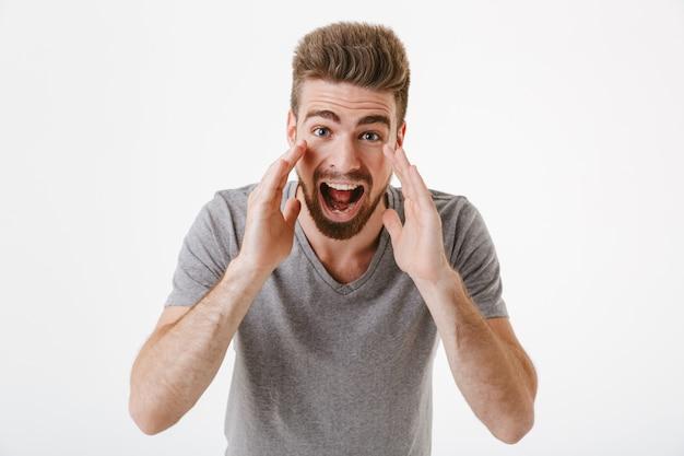 Ritratto di un giovane uomo barbuto eccitato che grida