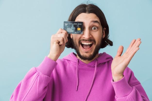 Ritratto di un giovane uomo barbuto eccitato che indossa abiti casual in piedi isolato sul muro, mostrando la carta di credito