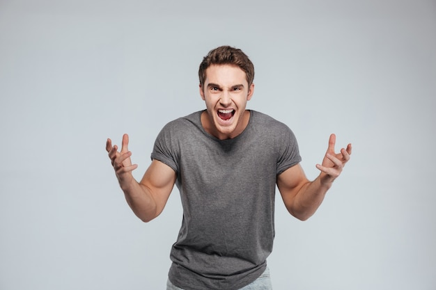 Ritratto di un giovane eccitato con entrambe le mani alzate sul grigio