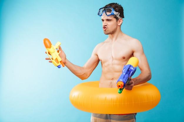 Ritratto di un giovane uomo a torso nudo eccitato in occhiali da nuoto