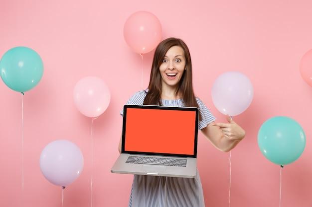 Ritratto di giovane donna eccitata in abito blu che tiene il dito indice puntato sul computer pc portatile con schermo vuoto vuoto su sfondo rosa pastello con mongolfiere colorate. festa di compleanno.