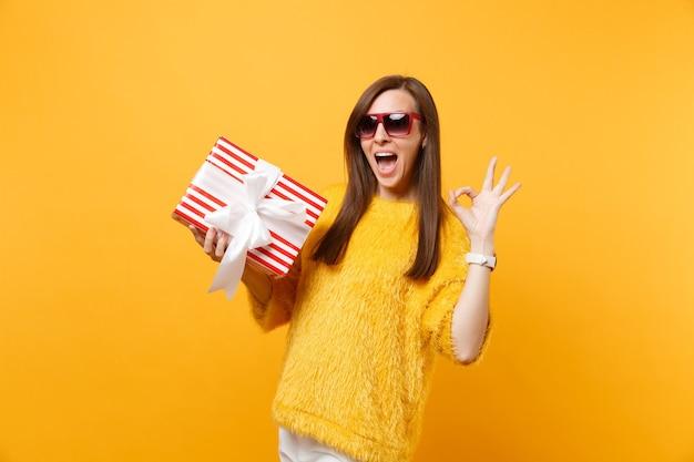 Ritratto di giovane donna eccitata in occhiali rossi che mostra segno ok che tiene scatola rossa con regalo, presente isolato su sfondo giallo brillante. persone sincere emozioni, concetto di stile di vita. zona pubblicità.