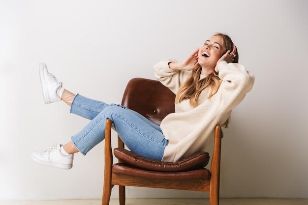 Ritratto di giovane donna eccitata che sorride e usa le cuffie mentre è seduto su una poltrona isolata su bianco
