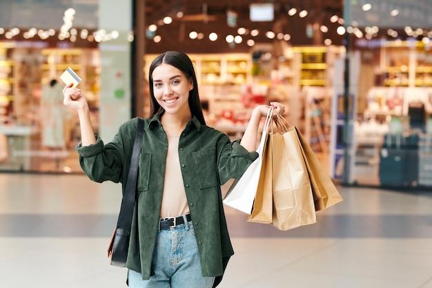 Ritratto di giovane donna eccitata con sacchetti di carta utilizzando la carta di credito durante lo shopping nel centro commerciale