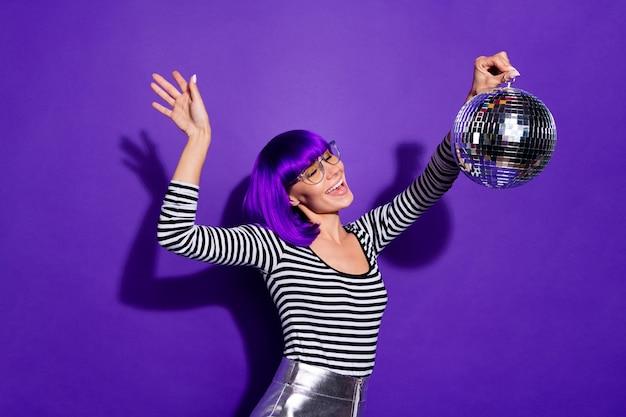 Ritratto di gioventù eccitata che tiene palla a specchio urlando in movimento indossando occhiali da vista isolati su sfondo viola viola