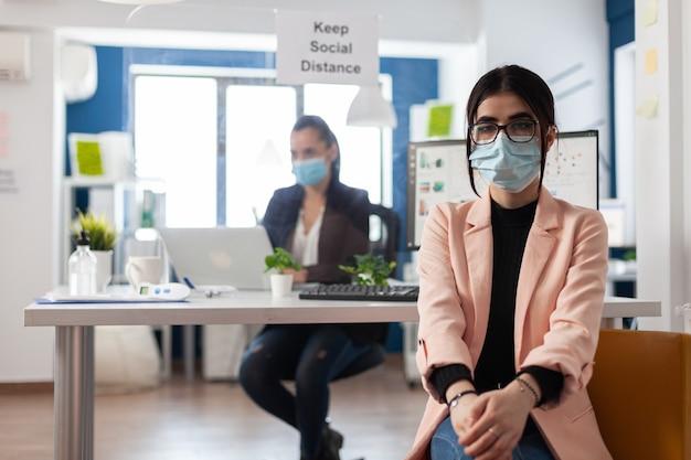 Ritratto di manager esecutivo che indossa una maschera protettiva medica contro il coronavirus che lavora nell'ufficio della società di avvio. strategia di gestione del brainstorming del lavoro di squadra durante la pandemia globale