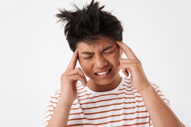 Ritratto di uomo asiatico esausto indossando t-shirt a righe accigliato e sfregamento tempie a causa di mal di testa, isolato