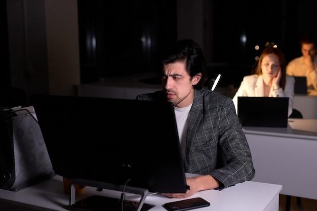 Ritratto di un maschio caucasico esausto preoccupato dal lavoro al computer in ufficio di notte, manca la scadenza, ha molti problemi, in una stanza buia, si siede a pensare. lavoro, concetto di affari