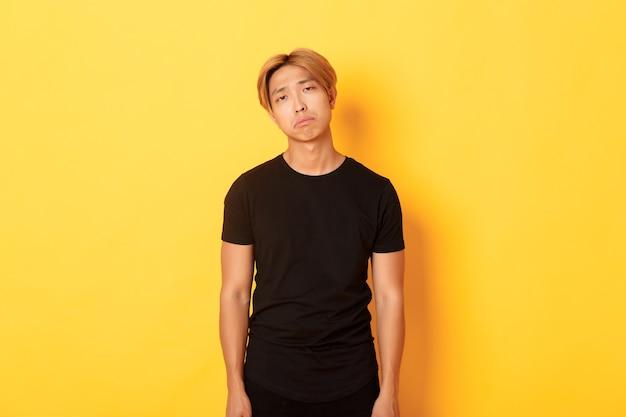 Ritratto di ragazzo asiatico esausto e triste che sembra triste, in piedi drenato sopra la parete gialla