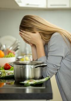 Ritratto di giovane casalinga esausta che posa sulla cucina mentre cucina la zuppa