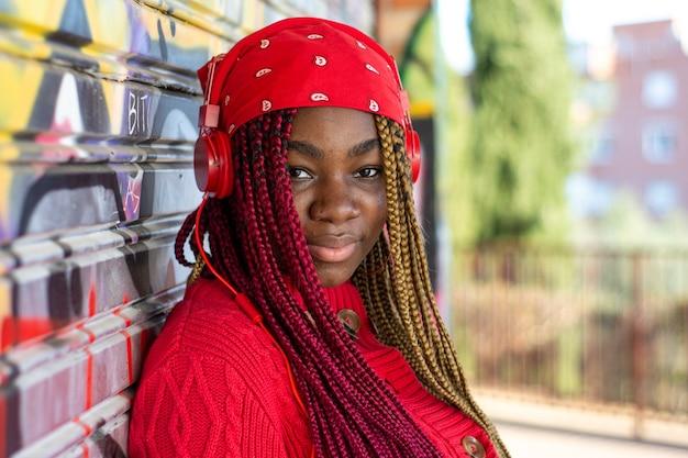 Ritratto di una ragazza nera esotica con trecce colorate. cuffie rosse che pendono dal collo. vestito con un maglione rosso e un velo rosso. sfondo muro di graffiti