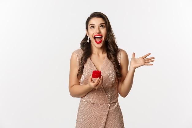 Ritratto espressiva giovane donna in abito elegante azienda scatola anello di fidanzamento