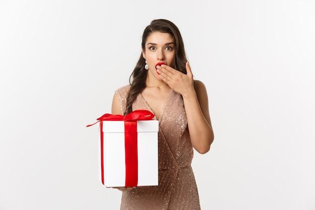 Ritratto espressiva giovane donna in abito elegante azienda confezione regalo
