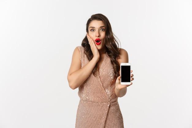 Ritratto espressiva giovane donna in abito elegante tenendo il telefono