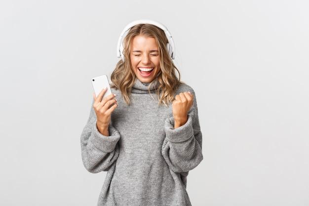 Giovane donna espressiva del ritratto con musica d'ascolto mobile