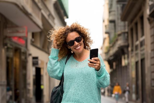 Ritratto f allegra adulta bella donna fare telefonata con la moderna tecnologia cellulare camminando per la strada nel concetto di città di attività per il tempo libero luogo urbano all'aperto e gente alla moda sorridente