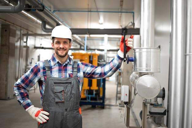 Ritratto dell'operaio dell'ingegnere di fabbrica che tiene il suo braccio sulla valvola e in piedi dal sistema di condutture di riscaldamento o raffreddamento al locale caldaia