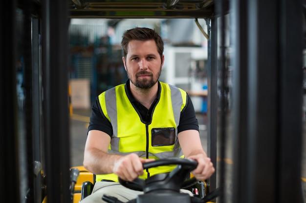 Ritratto dell'operaio che guida carrello elevatore