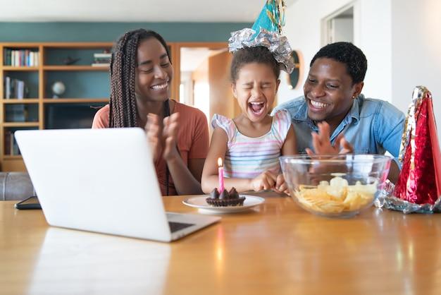 Ritratto di una famiglia che festeggia il compleanno in linea su una videochiamata mentre si resta a casa