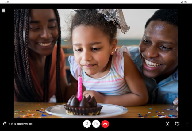 Ritratto di una famiglia che festeggia il compleanno online in una videochiamata con la famiglia e gli amici mentre si è a casa. nuovo concetto di stile di vita normale.