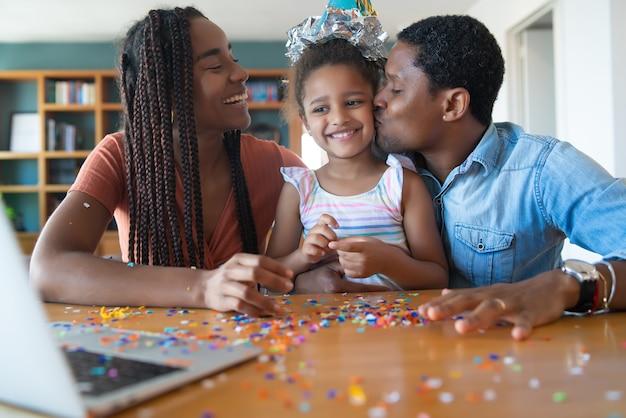 Ritratto di una famiglia che festeggia il compleanno online su una videochiamata con il laptop mentre si è a casa. nuovo concetto di stile di vita normale.