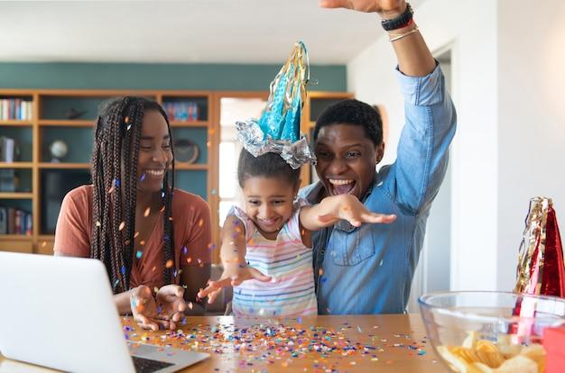 Ritratto di una famiglia che festeggia il compleanno in linea su una videochiamata con il laptop mentre si è a casa.