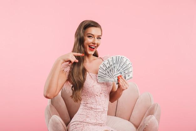 Ritratto di fantasia donna caucasica in abito che punta il dito sul ventilatore di soldi che tiene in mano mentre era seduto in poltrona, isolato sopra il muro rosa