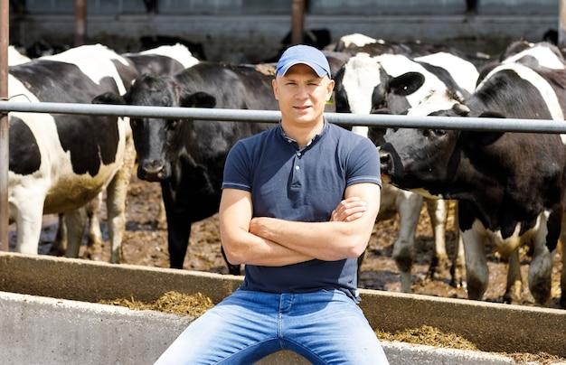 Ritratto di un contadino tra le mucche in una fattoria