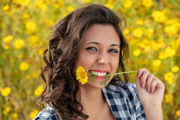Ritratto di ragazza affascinante divertendosi tra i fiori nel prato di primavera