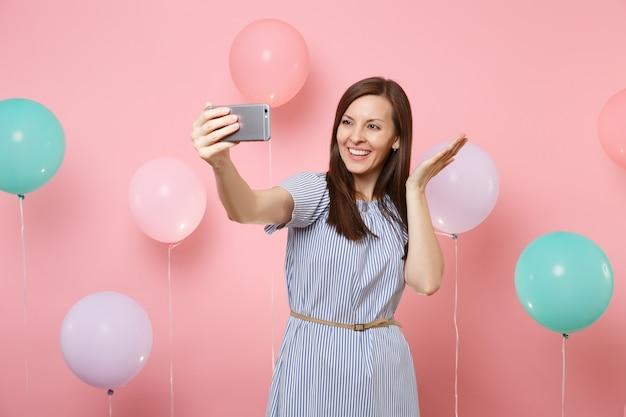 Ritratto di affascinante donna sorridente in abito blu che fa selfie sul telefono cellulare allargando le mani su sfondo rosa con mongolfiere colorate. festa di compleanno, concetto di emozioni sincere della gente.