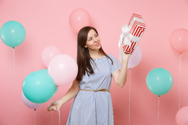 Ritratto di donna affascinante in abito blu che guarda una scatola rossa con un regalo che tiene in mano palloncini colorati su sfondo rosa di tendenza. festa di compleanno, concetto di emozioni sincere della gente.