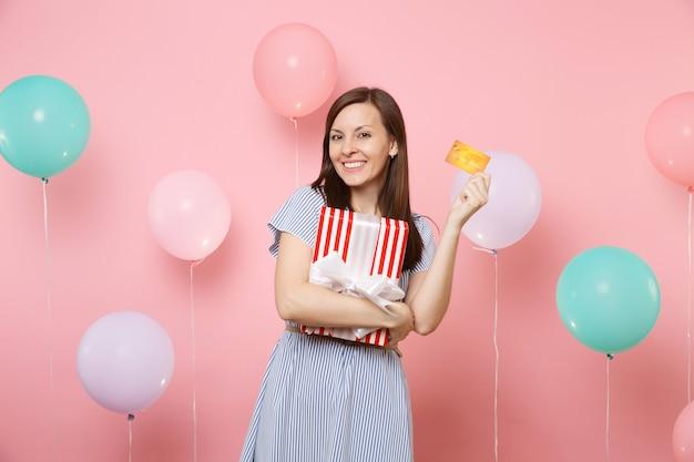 Ritratto di affascinante giovane donna in abito blu con carta di credito e scatola rossa con regalo presente su sfondo rosa pastello con mongolfiera colorata. festa di compleanno, emozione sincera di persone.