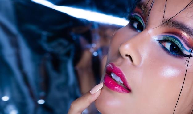 Portrait of fashion 20s asian woman ha un bellissimo aggiornamento make up artist, applica cosmetici alla moda per gli occhi, pose sensuali sexy su tonalità blu