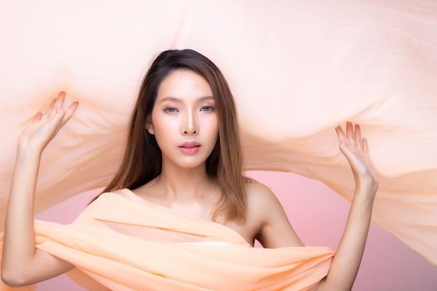 Portrait of fashion 20s asian woman ha un bellissimo trucco aggiornato e rossetto colorato, lancia svolazzanti vestiti arancioni