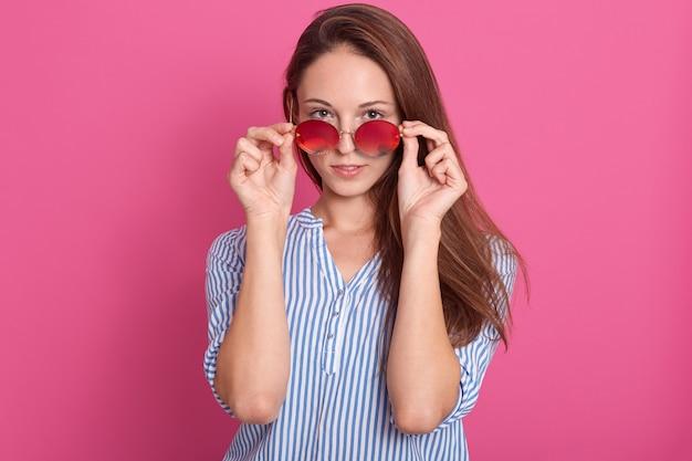 Ritratto della donna attraente di modo che dà una occhiata sopra gli occhiali da sole.