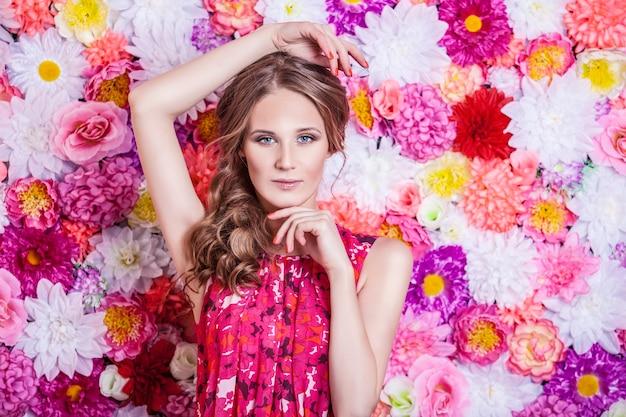 Ritratto di donna bella moda, dolce e sensuale con lussuoso makeover e capelli sui fiori di colori di sfondo