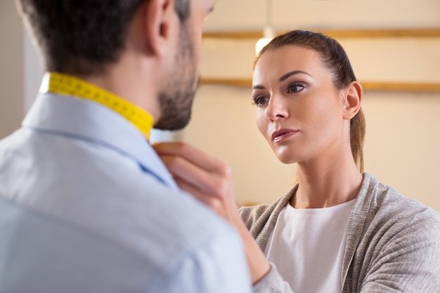 Ritratto dello stilista che misura il collo dell'uomo. sarto da donna della giovane donna ai sarti che fanno le misure. sarto che misura la taglia per un abito su misura per un giovane uomo d'affari.