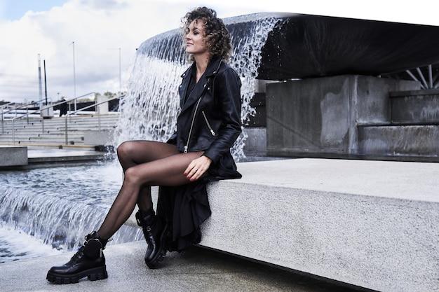 Ritratto di ragazza modello di moda in abiti neri seduti vicino alla fontana
