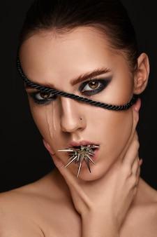 Ritratto di ragazza modello di moda con punte di metallo e trucco scuro.