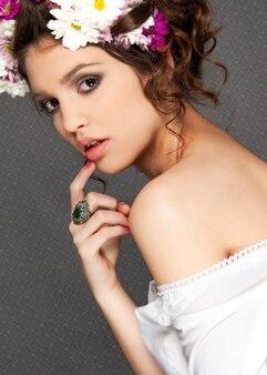 Ritratto di modella con trucco occhi smokey e corona di fiori