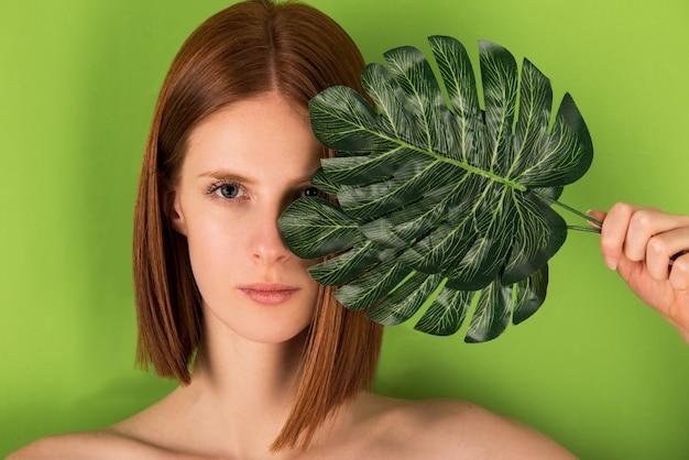 Ritratto di modella con capelli rossi che tiene in mano una grande foglia verde