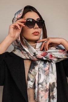 Ritratto di donna d'affari alla moda con sciarpa alla moda e occhiali da sole su sfondo grigio