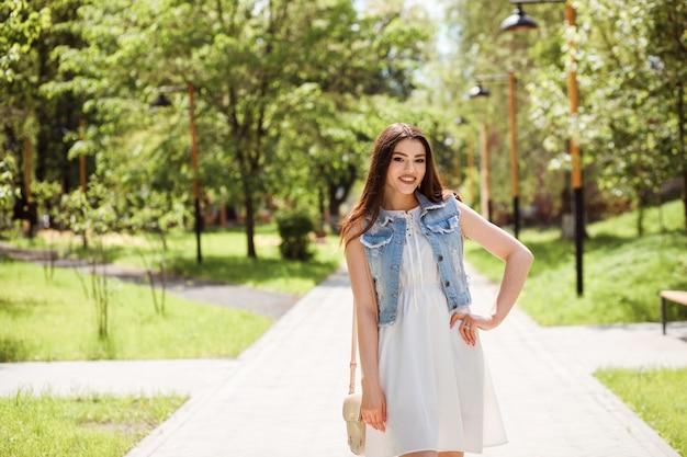 Ritratto di donna alla moda caucasica trascorrere del tempo all'aperto nel parco in estate. la ragazza è vestita in abito bianco e giubbotto di jeans.